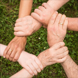 Dansk sammenhold. FOTO: Hænder som griber hinanden i en cirkel.