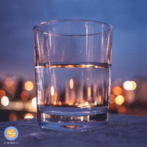 Foto af et halvt fyldt (eller halvt tomt) glas ved nattetide, med refleksioner af byens lys.