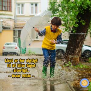 Billede af dreng, der leger i vandpyt. Livet er for vigtigt til at blive taget alvorligt. Citat af Oscar Wilde.